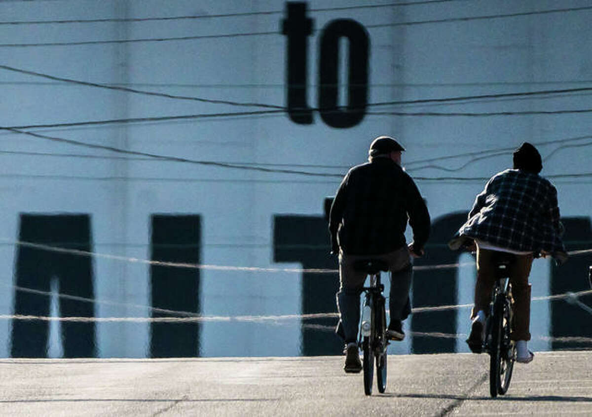 Two ride bicycles down an empty East Broadway in Alton.
