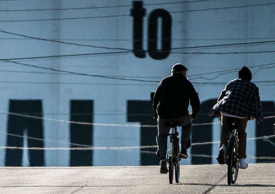 Two ride bicycles down an empty East Broadway in Alton. Photo: Nathan Woodside | The Telegraph