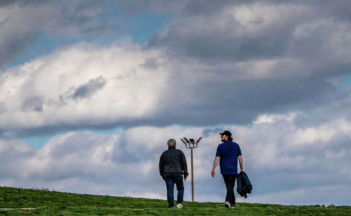 Two talk a walk near Liberty Bank Alton Amphitheater.