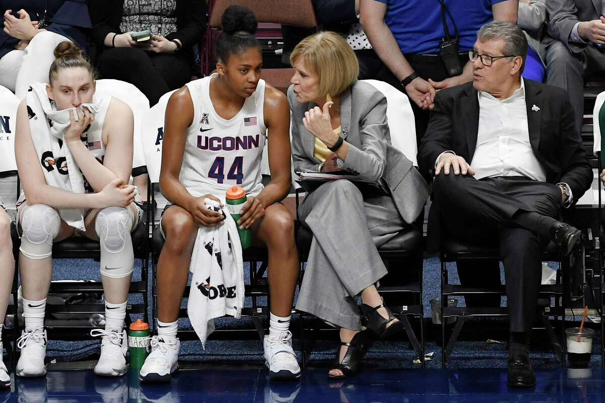 UConn's Aubrey Griffin (44) talks with associate head coach Chris Dailey as head coach Geno Auriemma, right, and Anna Makurat, left, watch during the second half of an American Athletic Conference tournament quarterfinal game against Temple at Mohegan Sun Arena in March.