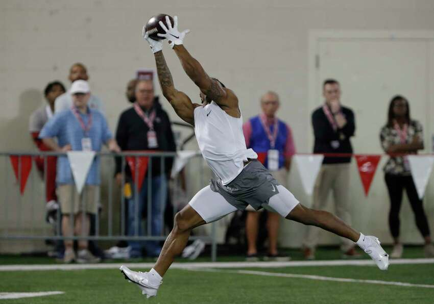 FILE - In this March 11, 2020, file photo, former Oklahoma running back Marcelias Sutton makes a catch as he runs through drills during Pro Day for NFL football scouts and coaches in Norman, Okla. Gone for the most part this year are access to in-person interviews, campus workouts and visits to team headquarters. Also gone are some of the numbers garnered at pro days decision makers like to crunch as they becoming increasingly reliant upon advanced metrics. (AP Photo/Alonzo Adams, File)