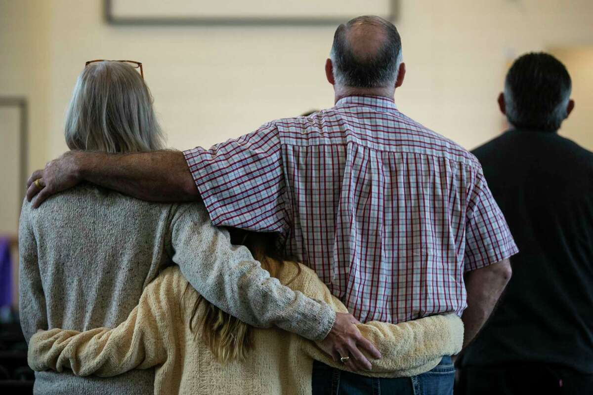 A holds onto each other during the worship portion of Sunday services at First Baptist Church in Sutherland Springs, Texas, April 5, 2020. First Baptist Church services have continued, despite CDC guidance to not have more than 10 people in a gathering, but congregants have the option to live stream the service from home. Pastor Frank Pomeroy said if the government forced the church to close its physical doors, he would file a constitutional lawsuit.