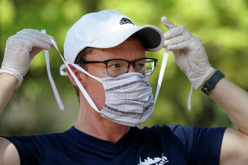 James Garcia-Parts puts on his mask as the reVision group holds a meeting after loading meals into their vehicles, at St. Luke United Methodist Church, 3471 Westheimer Rd., Thursday, March 26, 2020.