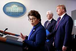 FILE - In this Thursday, April 2, 2020 file photo, Jovita Carranza, administrator of the Small Business Administration, speaks about the coronavirus in the James Brady Press Briefing Room of the White House n Washington, as Vice President Mike Pence, President Donald Trump listen. Millions of small businesses are expected to apply for a desperately needed rescue loan Friday, a stern test for a banking industry that has had less than a week to prepare for the deluge. Small businesses will be seeking loans from the $349 billion Paycheck Protection Program, which was put in place to help them retain workers and pay bills during the coronavirus pandemic. (AP Photo/Alex Brandon, File)