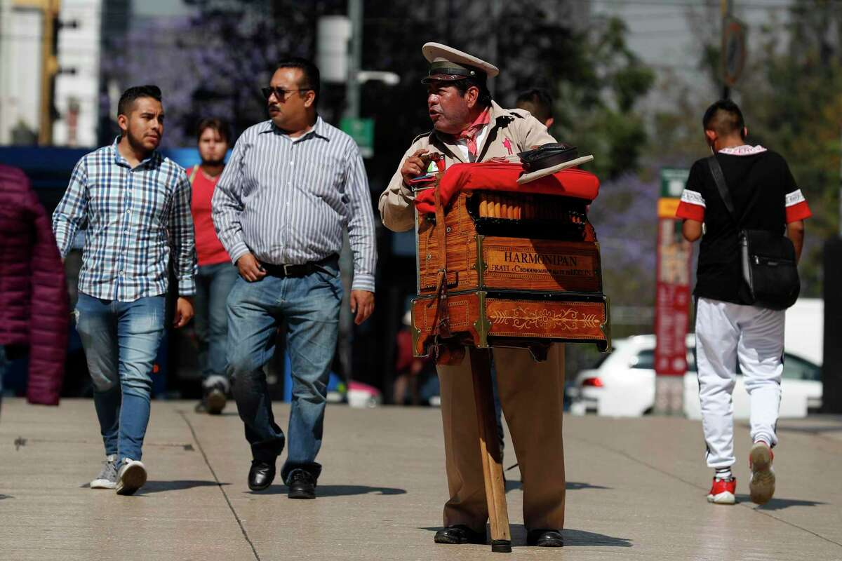 Organ grinder Moises Rosas solicits tips from pedestrians in central Mexico City in late March. Mexico has moved slowly to impose social distancing measures seen in other countires.