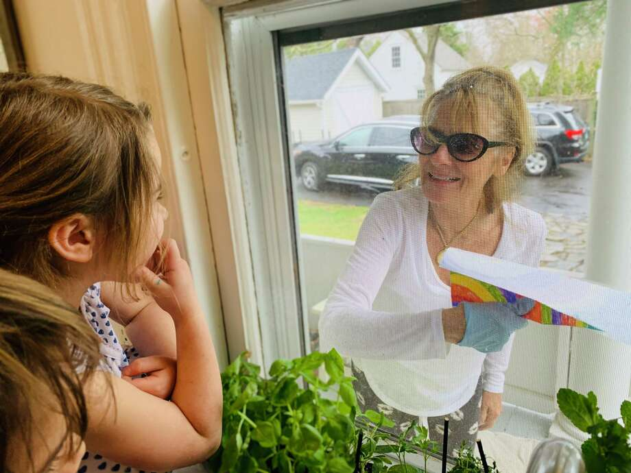 Emma Straus enjoying a moment with her First Congregational Church Nursery School teacher, Mrs. G. while receiving an assignment. (They were separated through the kitchen window) Photo: Contributed /