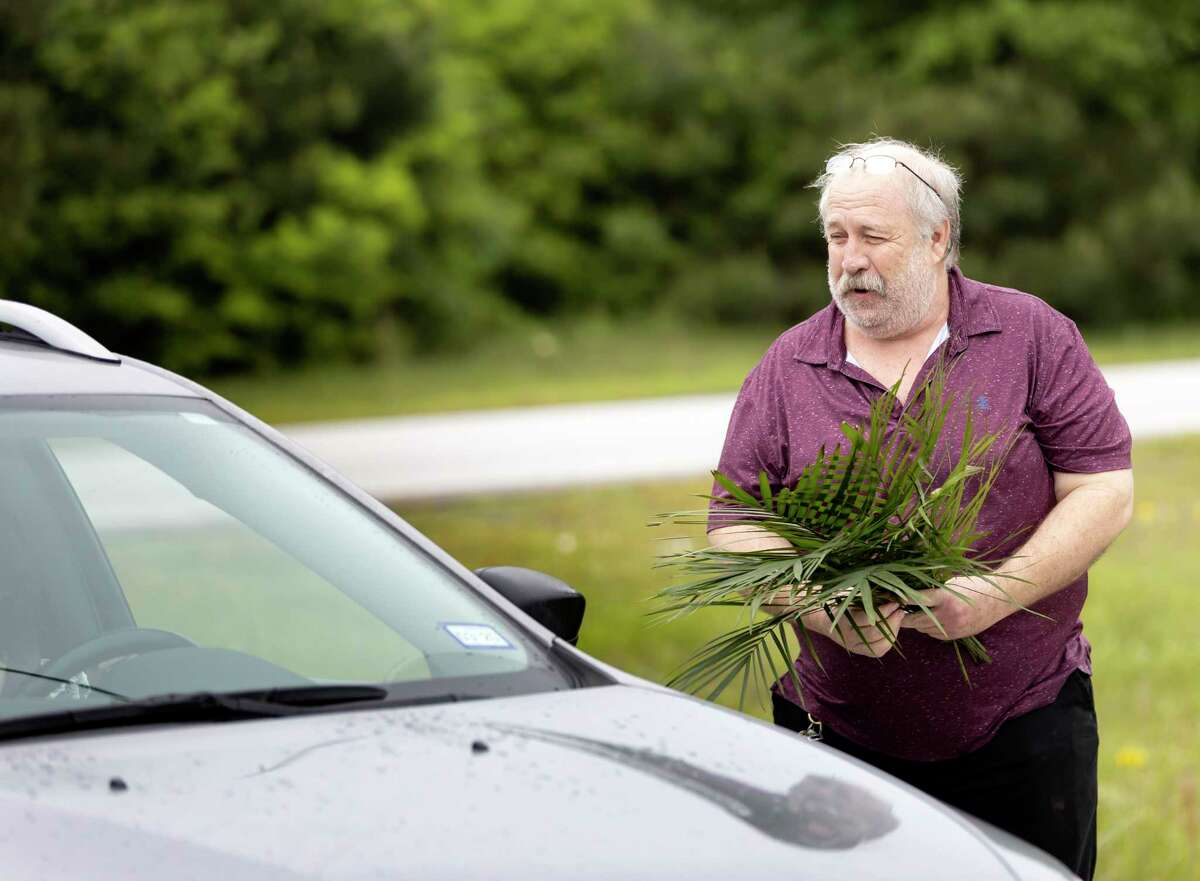 Carl Jones hands palm branches to church goers in Conroe, Sunday, April 5, 2020. Living Way United Methodist Church will continue drive-in services for the foreseeable future.