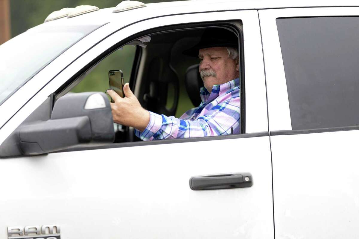 Jimmy Quimn live streams the drive-in Palm Sunday mass on his phone, Sunday, April 5, 2020. Living Way United Methodist Church will continue drive in services for the foreseeable future.