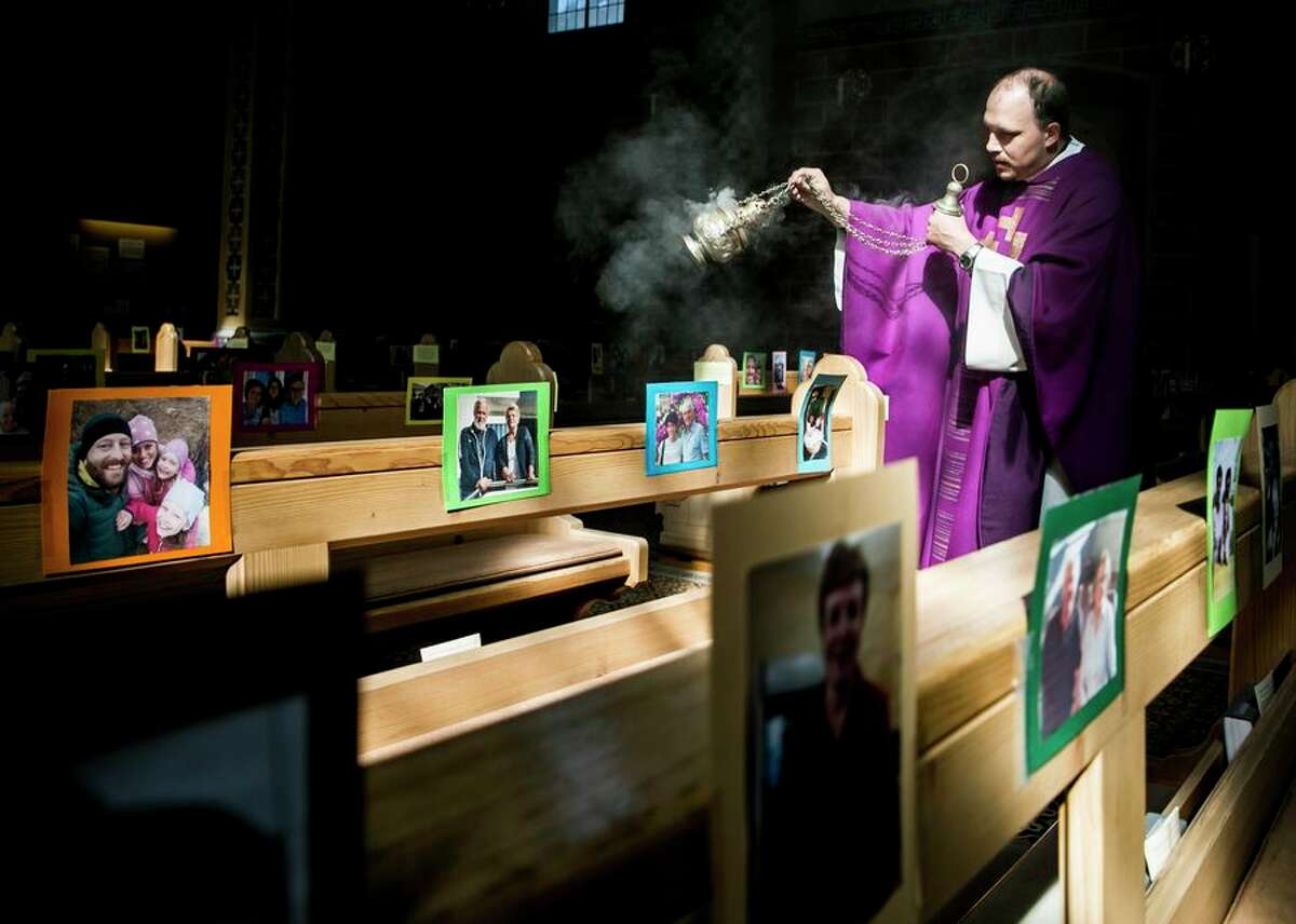 In Innsbruck, Austria, a Roman Catholic priest conducts mass in an empty church on April 6. The pews, though, hold hundreds of photos of parishioners, and the priest records the masses on video, then uploads them by evening for viewing by his congregation via the internet.