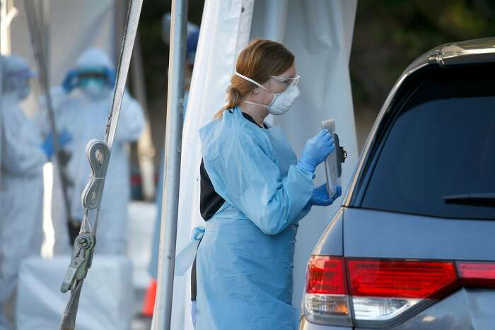 A health care worker speaks with a driver at a drive-thru coronavirus testing site in a parking lot of the old California Pacific Medical Center on California Street in San Francisco, Calif. on Thursday, April 2, 2020. The appointment only tests were provided for employees and staff of CPMC and Brown and Toland physicians.