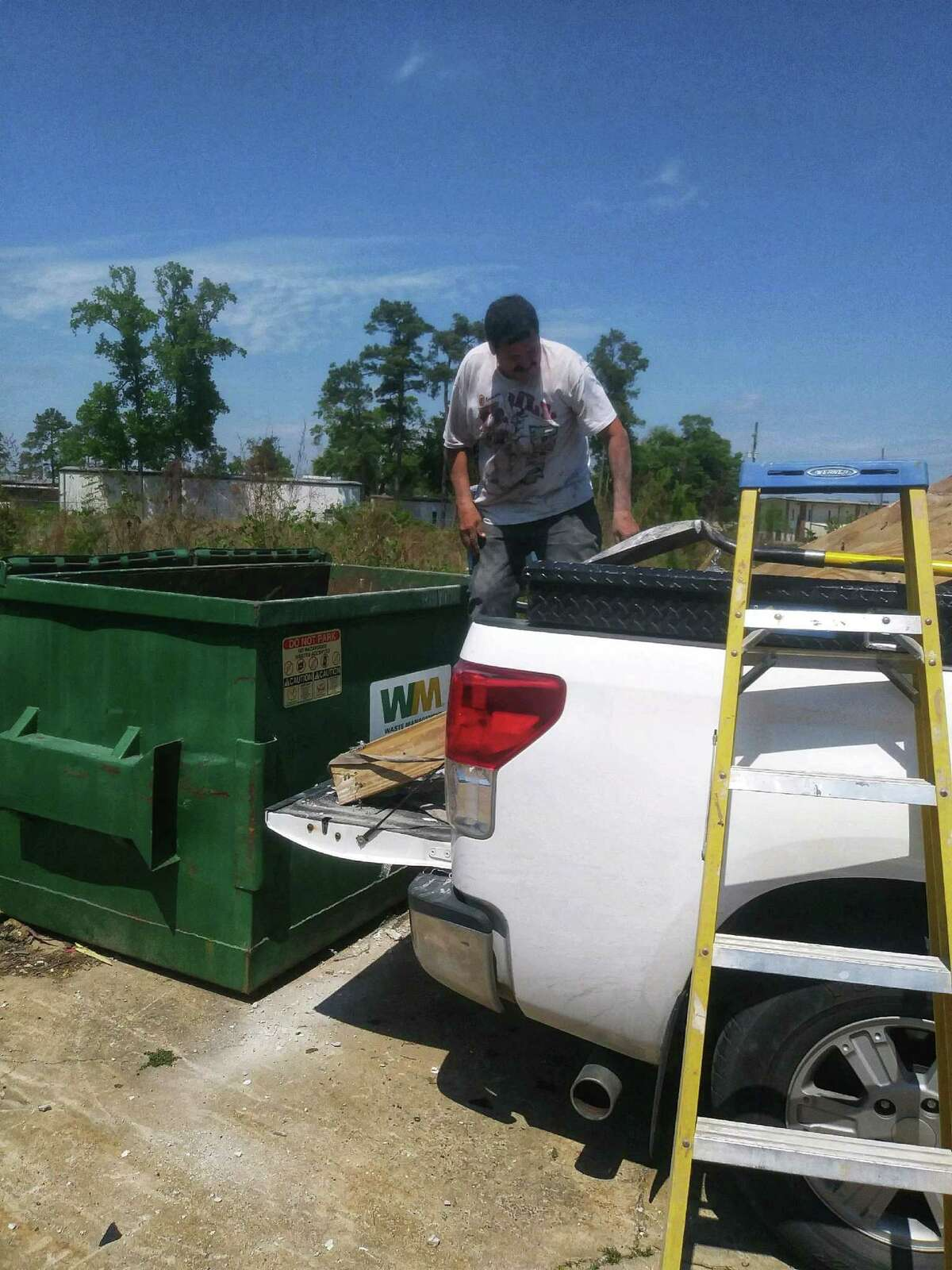Saul Olguín dumps debris in a garbage tank after finishing a job as a day laborer on March 26, 2020, in Houston.
