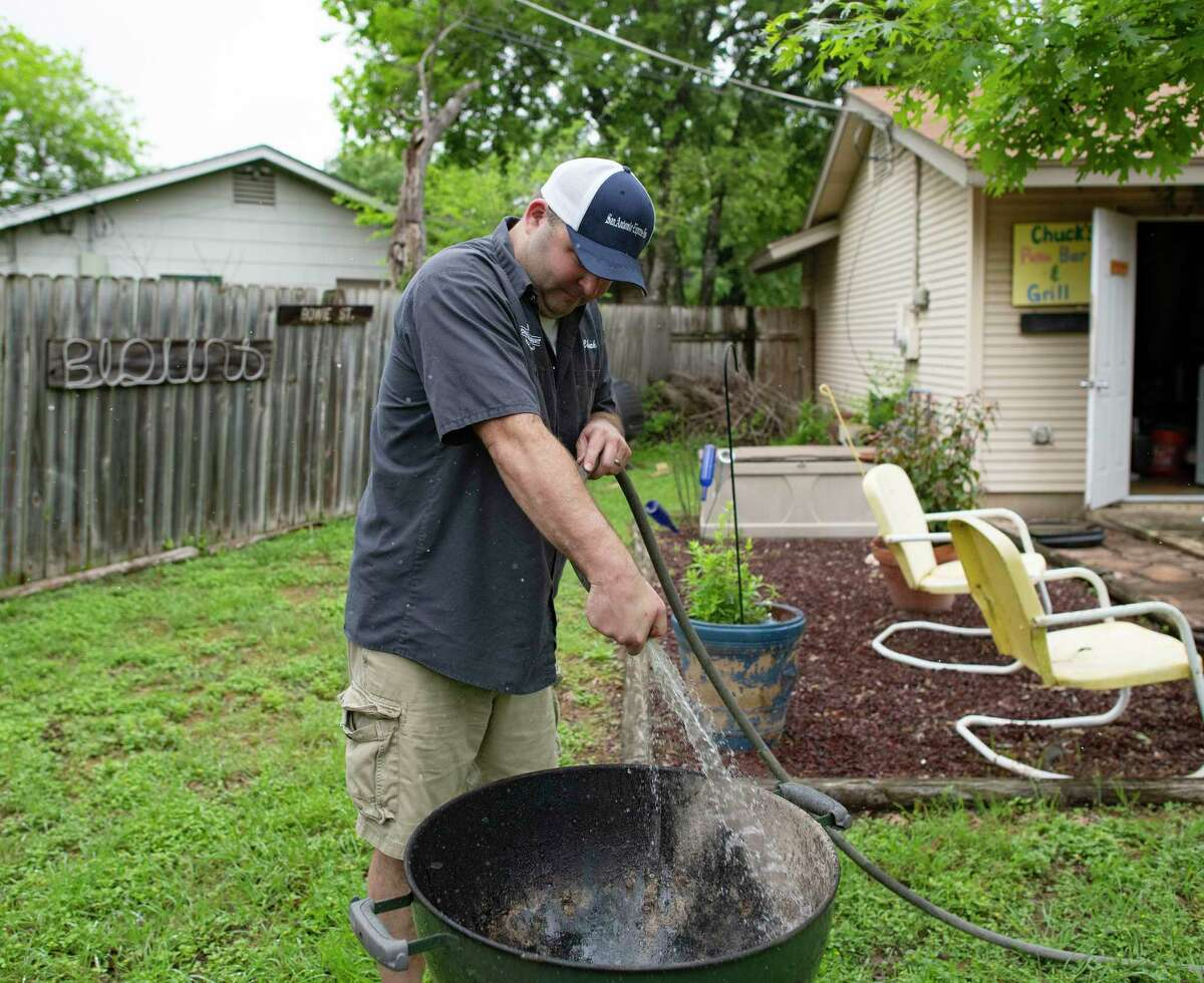 Chuck Blount washes down the base of his grill with a garden hose. Removing caked ash and grease regularly is a good way to extend the life of the grill, provided it's quickly dried with a towel.