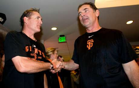 Dave Righetti (left) shakes the hand of Bruce Bochy as the San Francisco Giants celebrate their National League West Championship after defeating the San Diego Padres at AT&T Park on Sunday.