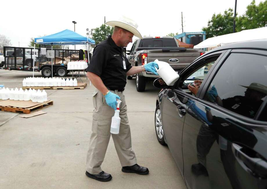Fort Bend County Sheriff Troy E. Nehls along with his officers hand out disinfectant to residents of Fort Bend County at the Fort Bend County Sheriff's Academy, in Richmond ,Sunday, March 22, 2020. Photo: Karen Warren, Houston Chronicle / Staff Photographer / © 2020 Houston Chronicle