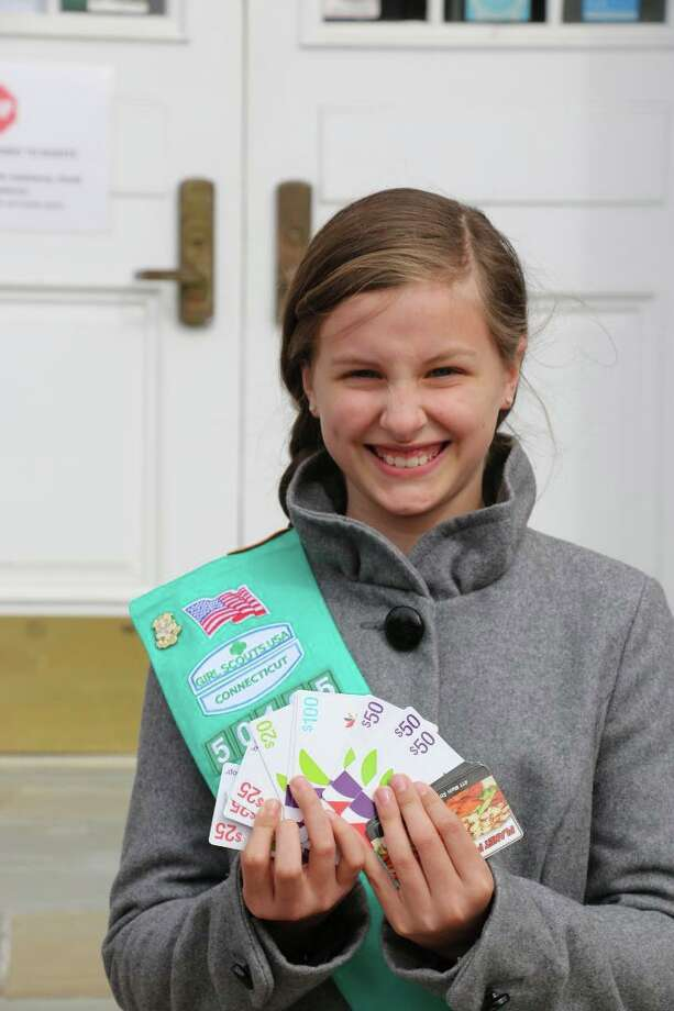 Girl Scout Maura McGuire recently donated gift cards to Ridgefield Food Pantry. Photo: Contributed Photo