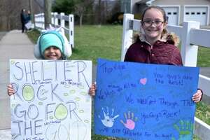 Anabella Sousa and Isabella Sousa hold signs to greet their Shelter Rock Elementary School teachers, who paraded in cars through their neighborhood on the morning of Saturday, April 4, 2020, in Danbury, Conn.