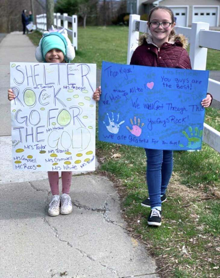 Anabella Sousa and Isabella Sousa hold signs to greet their Shelter Rock Elementary School teachers, who paraded in cars through their neighborhood on the morning of Saturday, April 4, 2020, in Danbury, Conn. Photo: Contributed Photo / The News-Times / The News-Times Contributed