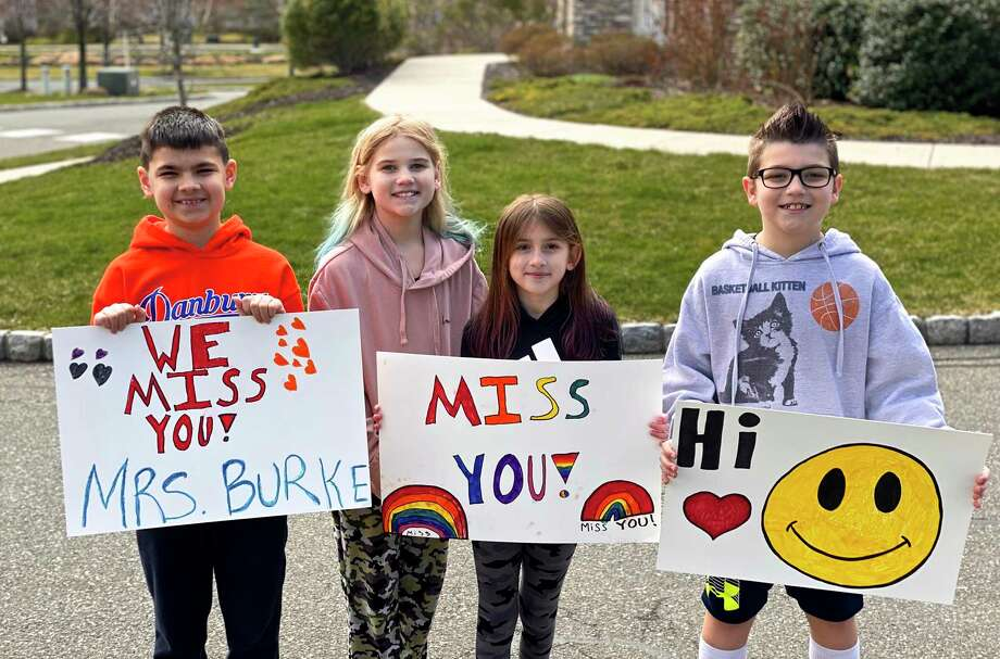 Nicholas Samperi, Hayden Schafer, Callie Samperi and Cole Schafer hold signs to greet their Shelter Rock Elementary School teachers, who paraded in cars through their neighborhood on the morning of Saturday, April 4, 2020, in Danbury, Conn. Photo: Contributed Photo / The News-Times / The News-Times Contributed