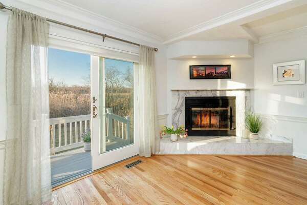 The living or family room has a marble fireplace and sliding doors to the deck and backyard.