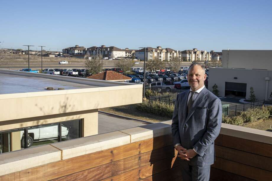 Colin Sewell, president of Sewell Family of Cos., poses on the balcony in front of his Ford dealership along State Highway 191 on March 5. Photo: Photos By Jacy Lewis