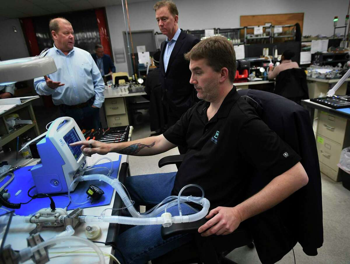 Gov. Ned Lamont, rear, tours Bio-Med Devices in Guilford, Conn., on March 29, 2020.