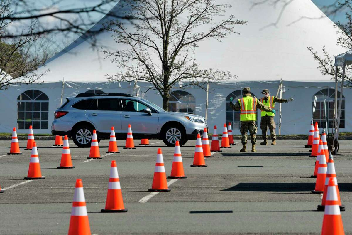 Members of the National Guard direct drivers arriving to be tested at the COVID-19 drive-through testing site at the University at Albany on Monday, April 6, 2020, in Albany, N.Y. The testing site is only for those who make appointments beforehand. (Paul Buckowski/Times Union)