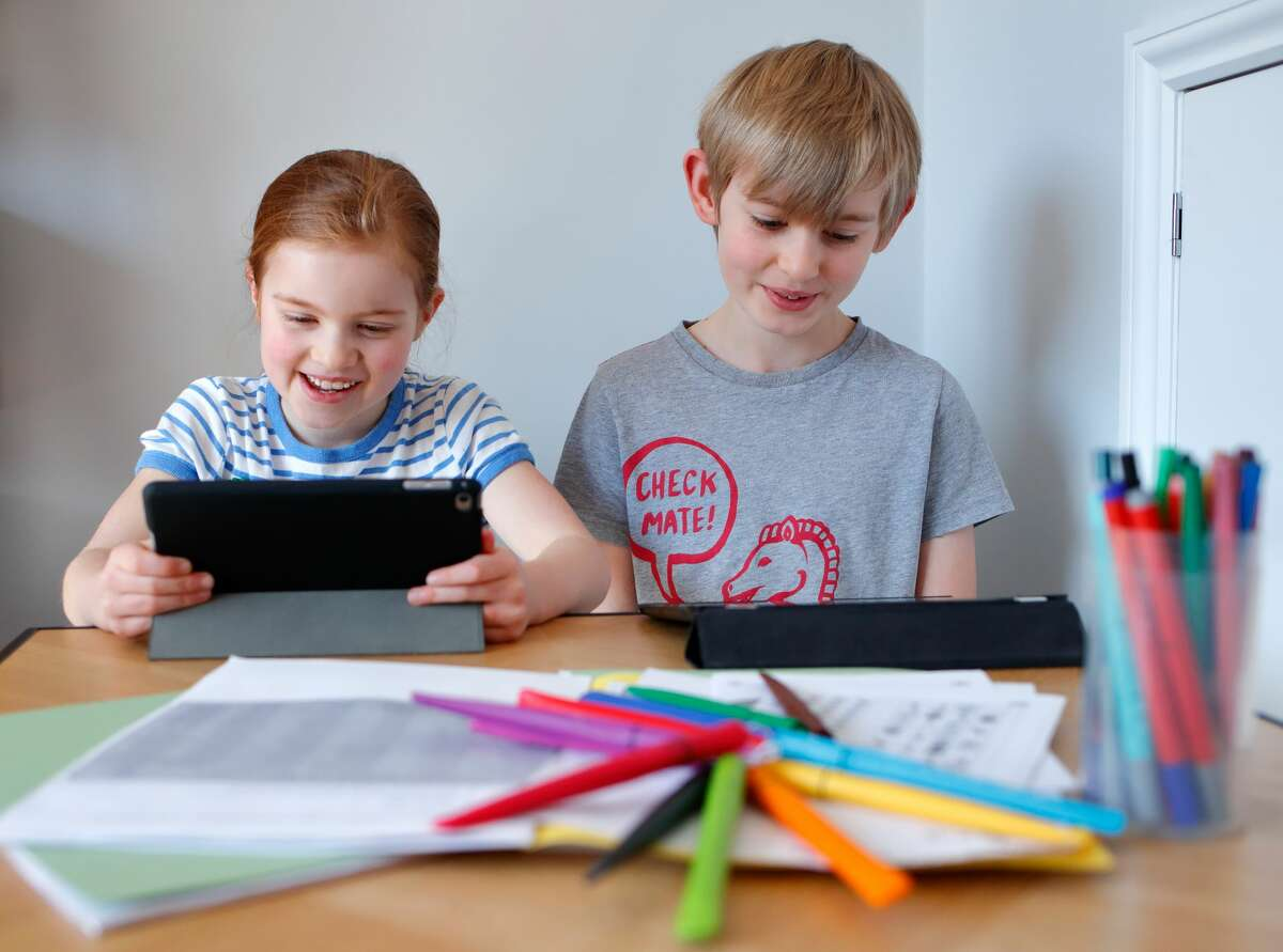 CUCKFIELD, UNITED KINGDOM - MARCH 22: In this photo illustration, school- age children of the photographer use iPads to complete online schoolwork at home whilst schools are closed due to the Coronavirus pandemic on March 22, 2020 in Cuckfield, England. As from Monday 23rd March 2020, UK Schoolchildren will work from home due to the COVID-19 Pandemic. Schools will open for children of Key workers. (Photo by Max Mumby/Indigo/Getty Images)