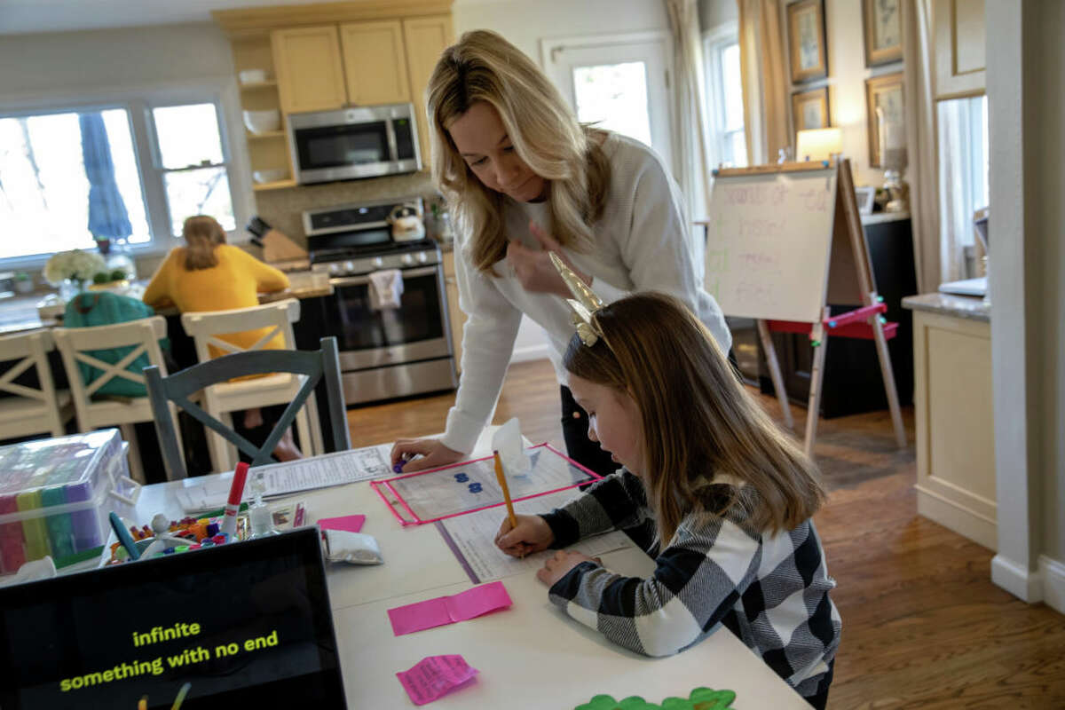 Farrah Eaton assists her daughter Nola, 6, with home schooling on March 18, 2020 in New Rochelle, New York.