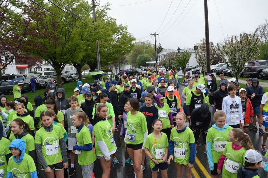 Hundreds line up in the rain for the start of the 2019 Circle of Care 5K/Run Walk to support families whose children have cancer. This year's race is going virtual. Photo: Jeff Salguero / Circle Of Care / Wilton Bulletin Contributed