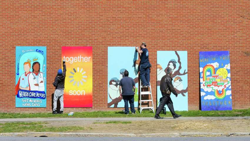 Tony Iadicicco, left, executive director of the Albany Center Gallery, touches up a mural as Albany Medical Center facilities staff hang another mural from the gallery on the outside wall of the medical center on Monday, April 6, 2020, in Albany, N.Y. Iadicicco, said that three of the pieces were created by local artists specifically for this project, as a way to express the community?•s gratitude and support for its health care workers. (Paul Buckowski/Times Union)
