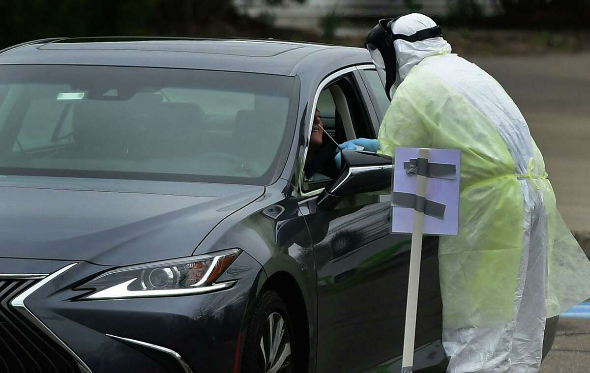 Workers with Murphy Medical Associates conduct corona virus at a drive-thru testing station Tuesday, March 31, 2020, at Bedford Middle School in Westport, Conn. Due to a large coronavirus outbreak in Westport, the Westport Weston Health District arranged for additional community testing. Residents of Westport and Weston were tested by Murphy Medical Associates, a private company, from 8:30 a.m. to noon.