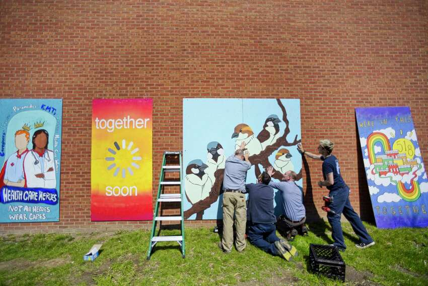 Albany Medical Center facilities staff hang murals from the Albany Center Gallery on the outside wall of the center on Monday, April 6, 2020, in Albany, N.Y. Tony Iadicicco, executive director of the gallery said that three of the pieces were created by local artists specifically for this project, as a way to express the community?•s gratitude and support for its health care workers. (Paul Buckowski/Times Union)