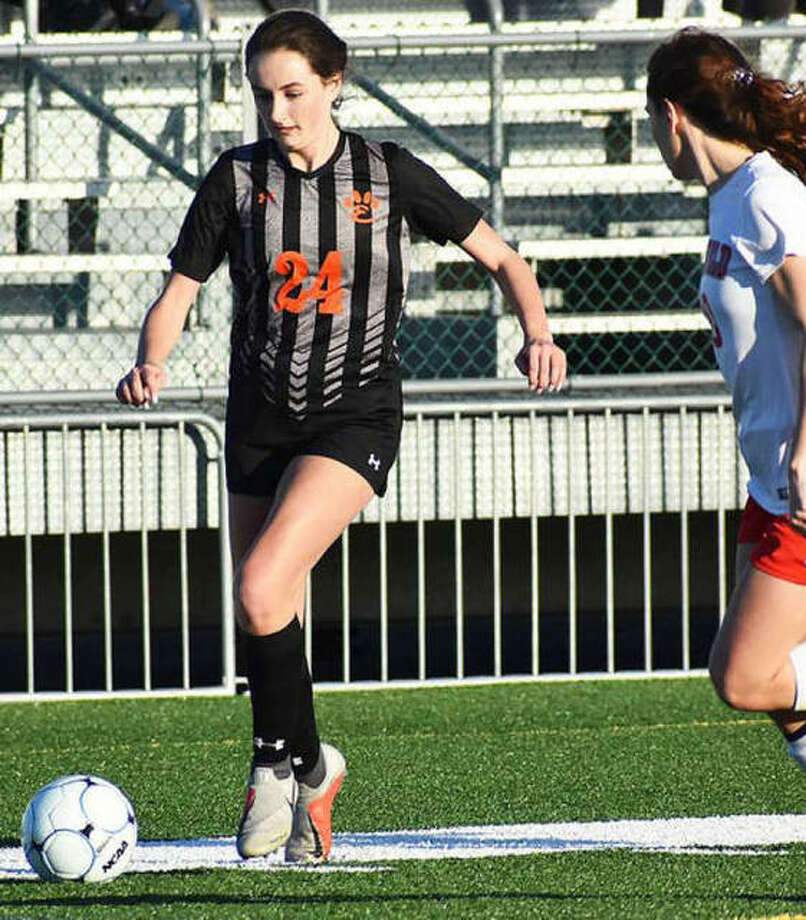 Edwardsville midfielder Rileigh Kuhns dribbles the ball down the field against a defender last season at home. Photo: Matt Kamp | For The Telegraph