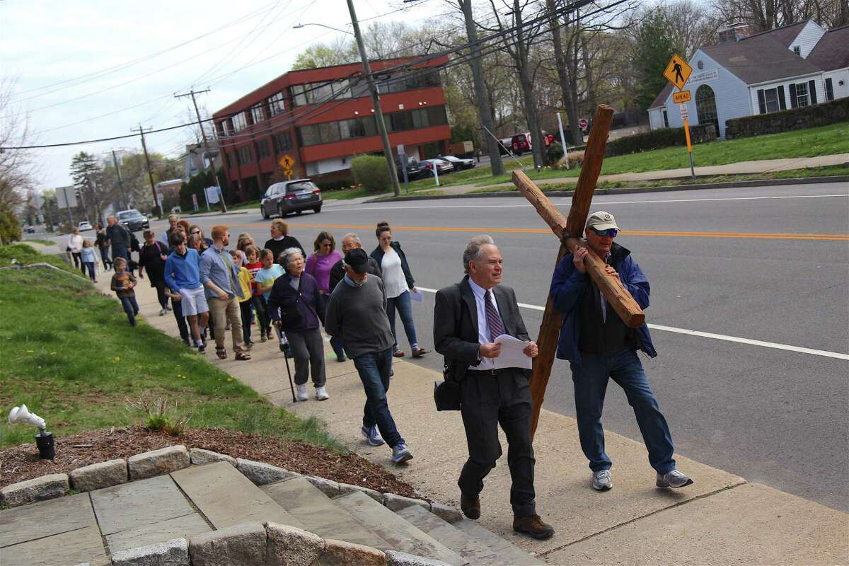 Rev. Dale Rosenberger, Senior Minister at The First Congregational Church of Darien, walks with Lance Minor carrying the cross at a previous Cross Walk in 2019.