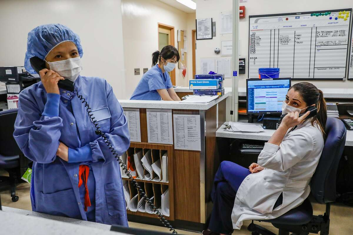 Nurses Regina Truong (left) and Liz Philips (right) talk on the phone as they work on the Covid-19 floor at Saint Francis Hospital in San Francisco on Monday, April 6, 2020.