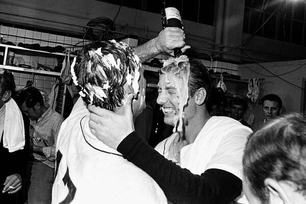 "FILE - In this Sept. 17, 1968, file photo, Detroit Tigers pitcher Denny McLain, his head covered in shaving cream, pours a bottle of champagne over the head of teammate Al Kaline as they celebrate their American League pennant victory in the dressing room in Detroit. Al Kaline, who spent his entire 22-season Hall of Fame career with the Detroit Tigers and was known affectionately as ""Mr. Tiger,"" has died. He was 85. John Morad, a friend of Kaline's, confirmed to The Associated Press that he died Monday, April 6, 2020, at his home in Michigan. (AP Photo/File)"