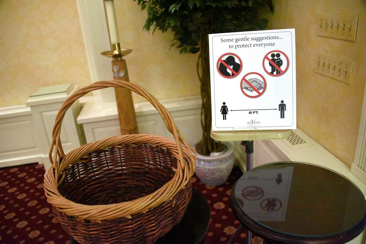 Social distancing signage is seen in McVeigh Funeral Home on Monday, April 6, 2020 in Albany, N.Y. Funeral homes now have to get creative when planning services since the coronavirus spread. (Lori Van Buren/Times Union)