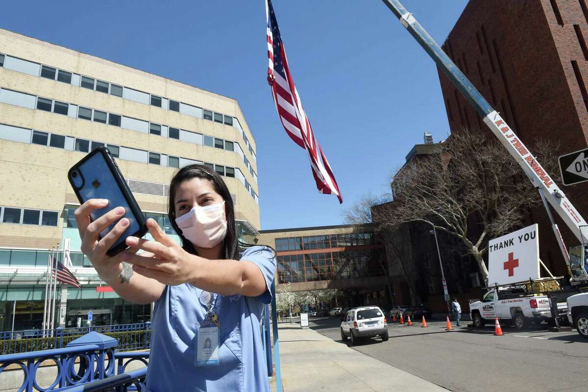 Patient Care Associate Ashlee Tarsia takes a selfie in front of a 50-foot United States flag and thank you put up by Kyle DeLucia, founder and owner of K&J Tree Service, in front of Yale New Haven Hospital on April 6, 2020. DeLucia put up the flag and a large thank you across from the hospital on York Street to show his appreciation for the work of the hospital staff.