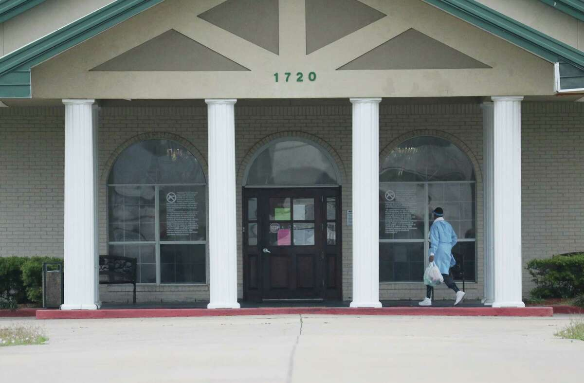 A person wearing PPE walks into The Resort at Texas City, a nursing home where 80 residents and employees have tested positive for the new coronavirus, on Friday, April 3, 2020, in Texas City. Galveston county health district announced late Thursday that it had tested 146 residents and employees at The Resort after finding that 13 residents and employees tested positive for the virus last weekend.