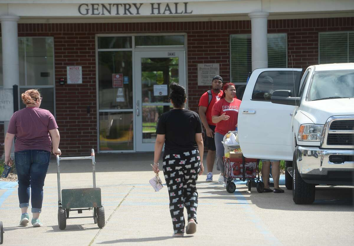 Lindsey Hendrix (left) pulls a cart as she moves out with help from best friend Jasmine Delarosa-Bonilla, who will be staying at Gentry Hall, as she packs up to return home to Anahuac at Lamar University Tuesday. Photo taken Tuesday, March 31, 2020 Kim Brent/The Enterprise