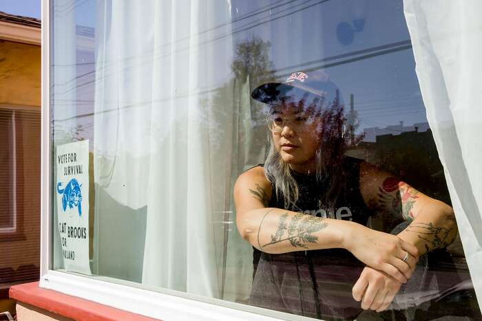 Olivia Lee of the band Theres Talk poses for a portrait in the window of her home in San Francisco, Calif. Tuesday, March 31, 2020. �I have been moving through such deep, visceral waves of grief with this whole thing. But it�s firing up our activist spirits and we�re all digging down into what we can all offer each other, our marginalized communities, and folx hurting & really at a loss right now,� says Lee. �I live in a queer organizer and musician house and community care is part of our ecosystem. We all kicked into gear immediately. I started raising & dispersing funds for queer musicians, and my roommates started a livestream show to showcase & support artists. We joked about it, but we are applying polyamory negotiation principals to our house meetings. And we�re dividing tasks up and creating a sort of emotional equilibrium of care when things are too much for one of us to handle. And there is also huge lightness still� singing over soup in the kitchen, lending butter so baked goods can be made and delivered, everyone on calls in separate rooms. There is such a bustling, bursting joy and aliveness.�