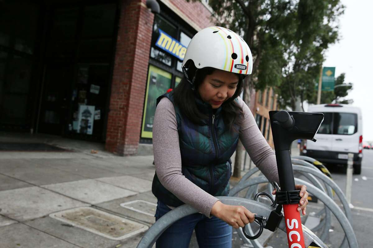Emily Calangian, Scoot accountant, demonstrates how to lock a Bird Kick scooter on Friday, December 13, 2019 in San Francisco, Calif.