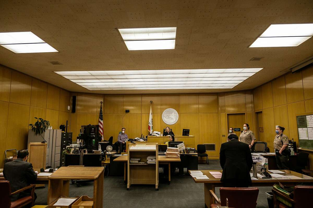 Officers of the court are seen practicing social distancing before Judge Loretta Giorgi presides over court cases in San Francisco, Calif. on Friday April 3, 2020.