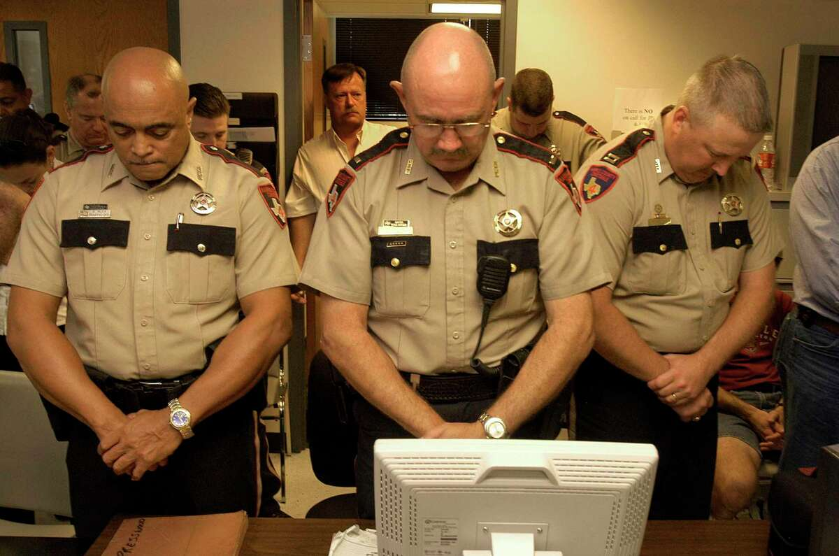 Deputy Stephen Alex, Lieutenant Brian Magee, and Captain Mark Herman pray before a meal at Precinct 4 in Spring in 2005. Magee, 66, who worked at the federal courthouse in Houston, died early Monday at his home in Spring.