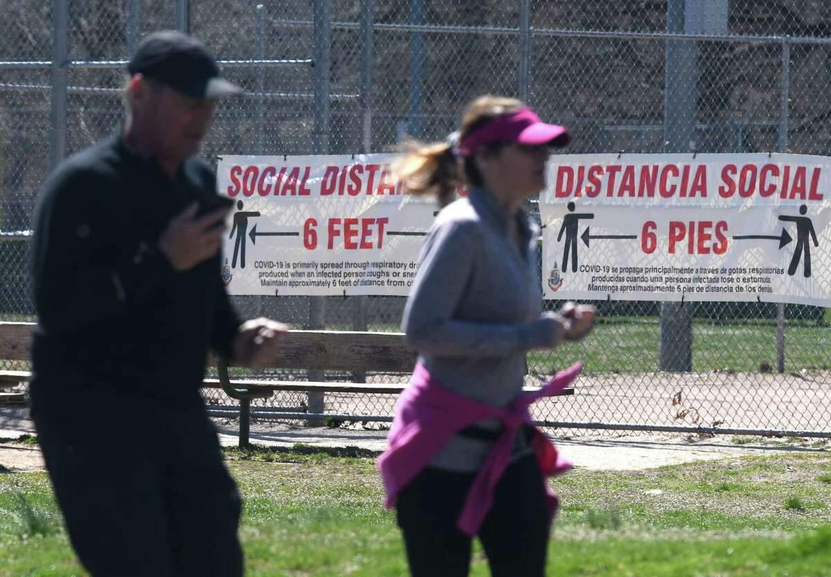 Joggers run laps as a sign promoting social distancing is displayed behind them on a fence at Scalzi Park in Stamford, Conn. Monday, April 6, 2020. Doctors recommend keeping a distance of at least six feet away from others to reduce the risk of contracting the coronavirus.
