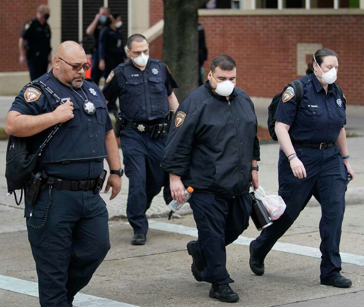 Harris County Sheriff's employees are shown walking near the Harris County Jail at the intersection of Baker St. and N. San Jacinto St., Monday, April 6, 2020, in Houston. Amid the coronavirus pandemic, a number of Harris County Sheriff's deputies, detention officers and staff have tested positive for COVID-19.