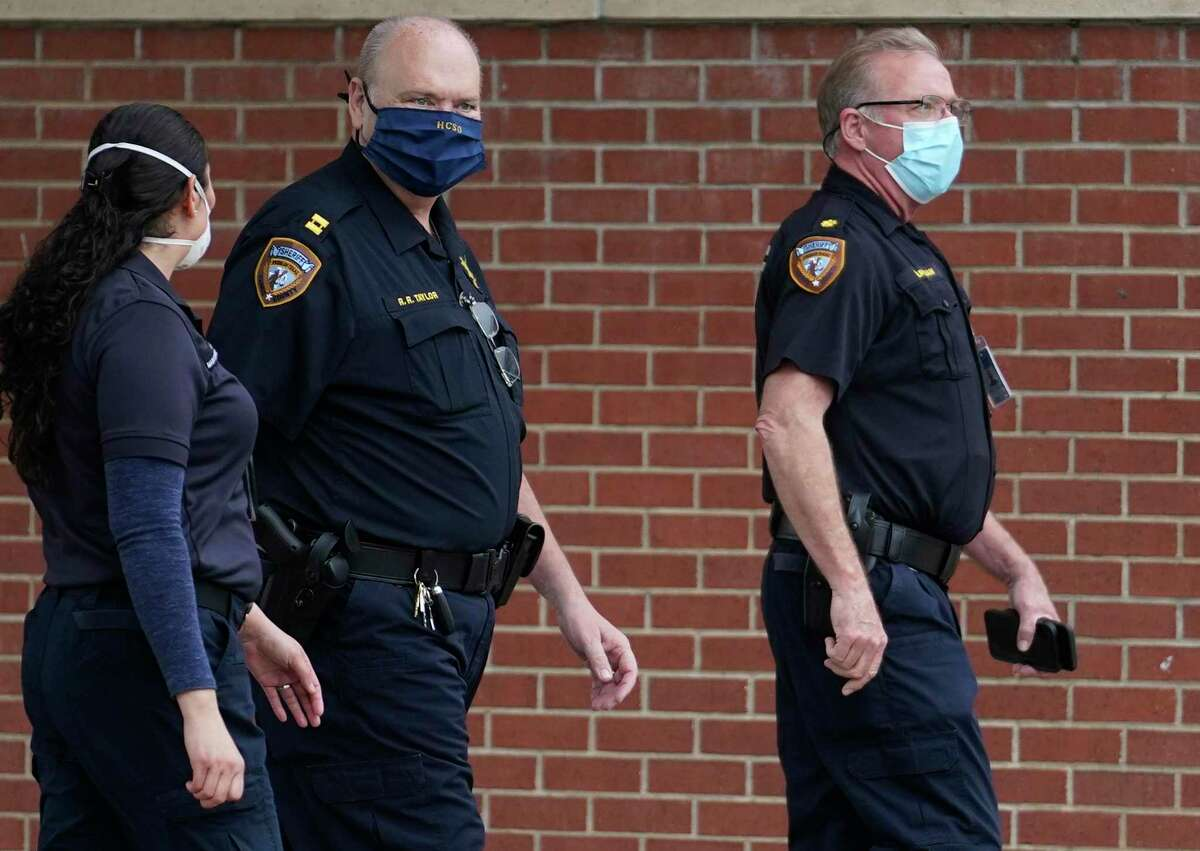 Harris County Sheriff's employee are shown walking near the Harris County Jail at the intersection of Baker St. and N. San Jacinto St., Monday, April 6, 2020, in Houston. Amid the coronavirus pandemic, a number of Harris County Sheriff's deputies, detention officers and staff have tested positive for COVID-19.