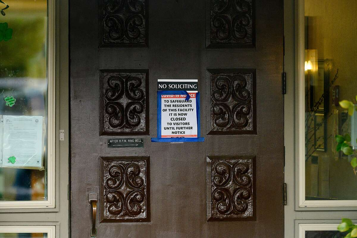 A sign hangs on the door at Orinda Care Center, where nearly 50 residents and staff members have tested positive for coronavirus, on Monday, April 6, 2020, in Orinda, Calif.