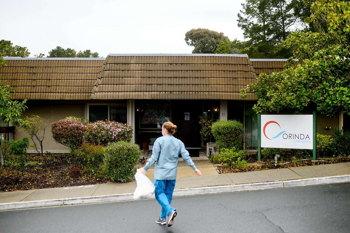A nurse from John Muir Medical Center prepares to enter Orinda Care Center in April, where dozens of residents and workers tested positive for coronavirus.