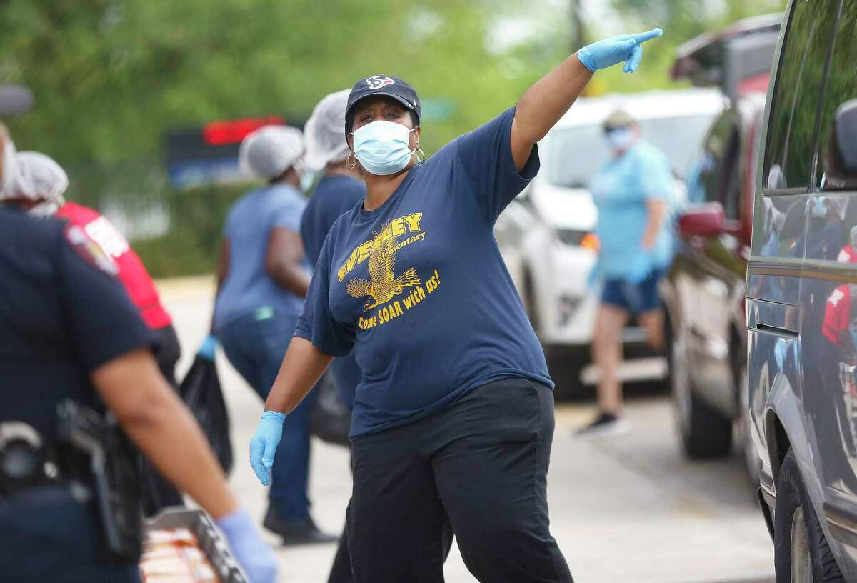 Workers pass out food in front of Houston ISD's Welsey Elementary School on Monday, April 6, 2020. HISD restarted food distribution Monday at five campuses after concerns arose in late March about worker safety.